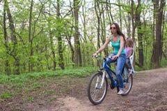 Велосипед матери и маленькой дочери задействуя на парке Стоковое Изображение RF