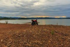 Велосипед мотора взгляда с заходом солнца на береге реки Стоковые Изображения RF