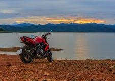 Велосипед мотора взгляда с заходом солнца на береге реки Стоковое фото RF