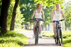 Велосипед 2 молодых женщин Стоковая Фотография RF