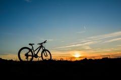 Велосипед на заходе солнца на поле Стоковые Изображения