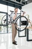Велосипед нося кавказского бизнесмена стоя и в современном офисе Стоковые Изображения
