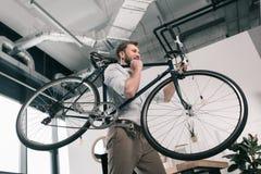Велосипед нося кавказского бизнесмена стоя и в современном офисе Стоковое Фото
