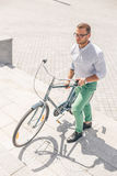 Велосипед нося молодого стильного бизнесмена вверх по шагам Стоковая Фотография
