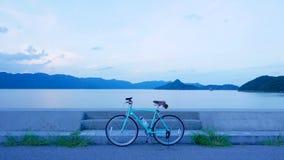 Велосипед, дорога, облако и озеро Стоковая Фотография RF