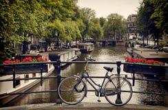 Велосипед припаркованный на пешеходном мосте обозревая канал в Амстердаме стоковая фотография rf