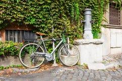 Велосипед припаркованный около выпивая крана на улице в Риме Стоковое Изображение RF