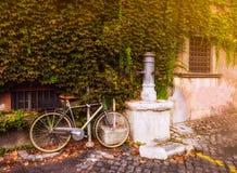 Велосипед припаркованный около выпивая крана на улице в Риме Стоковые Изображения RF