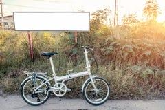 Велосипед складчатость припаркованная на луге с белым плакатом стоковое изображение
