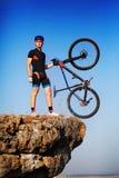 Велосипед удерживания велосипедиста человека на верхней части холма против красивого голубого неба Стоковые Изображения