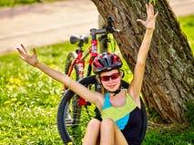 Велосипед шлем ребенка нося Девушка в задействуя сидеть около велосипеда Стоковая Фотография RF