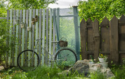 Велосипеды в саде на предпосылке загородки дерева стоковое фото rf