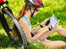 Велосипеды задействуя шлем девушки нося в задействуя сидеть около таблетки ПК велосипеда и вахты Стоковое Фото