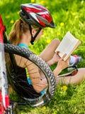 Велосипеды задействуя шлем девушки нося прочитали книгу на остатках около велосипеда Стоковые Изображения