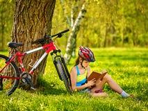 Велосипеды задействуя шлем девушки нося прочитали книгу на остатках около велосипеда Стоковое фото RF
