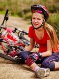 Велосипеды задействуя шлем девушки нося упали с велосипеда стоковые фотографии rf