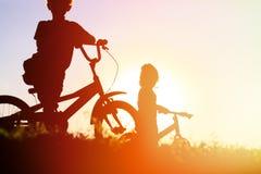 Велосипеды катания мальчика и девушки на заходе солнца Стоковая Фотография RF