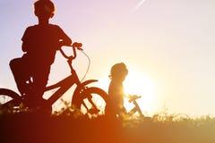 Велосипеды катания мальчика и девушки на заходе солнца Стоковые Фото