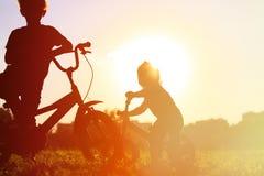 Велосипеды катания мальчика и девушки на заходе солнца Стоковая Фотография