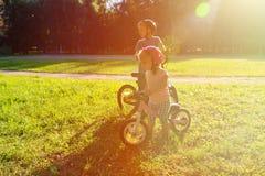 Велосипеды катания мальчика и девушки на заходе солнца Стоковое Изображение RF