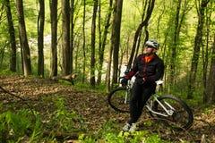 Велосипеды человека в зеленом лесе Стоковое Изображение