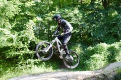 Велосипед moutain молодого человека практикуя в лесе Стоковые Фотографии RF