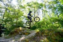 Велосипед moutain молодого человека практикуя в лесе стоковое изображение