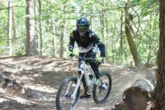 Велосипед moutain молодого человека практикуя в лесе Стоковое фото RF