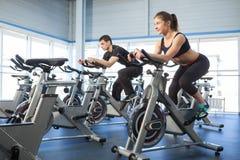 Велотренажеры человека и женщины на спортзале Стоковое Фото