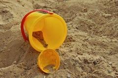 Ведро и прессформа желтых детей, лежа в ящике с песком Стоковые Изображения