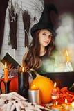 Ведьма около боилера с книгой Стоковые Изображения RF