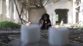 Ведьма с длинными руками черных волос развевая вызывая духи с черной магией и свечами видеоматериал