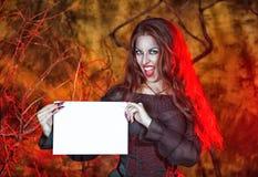 Ведьма хеллоуина держа лист бумаги стоковая фотография rf