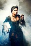 Ведьма хеллоуина создает волшебство Привлекательная женщина в костюме ведьм с куклой voodoo в руке Стоковые Фото