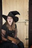 Ведьма хеллоуина с книгой стоковые изображения