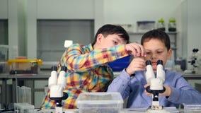 Взаимная работа молодых мальчиков ученых в лаборатории Конец-вверх 4K видеоматериал