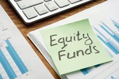 Взаимные фонды акций написанные на куске бумаги стоковые изображения