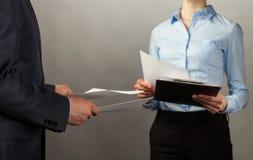 Взаимообмен бизнесмена и коммерсантки документов Стоковые Фото
