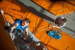 Взбираться мужского утес-альпиниста практикуя на стене утеса внутри помещения Стоковое Изображение