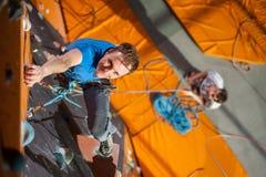 Взбираться мужского утес-альпиниста практикуя на стене утеса внутри помещения Стоковые Фотографии RF