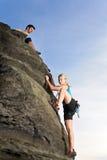 взбираясь веревочка утеса человека владением вверх по женщине Стоковое фото RF