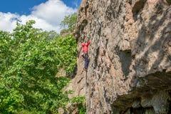 взбираясь утес узлов ropes 2 Молодой альпинист взбирается вертикальный утес гранита весьма спорт Стоковое Изображение RF
