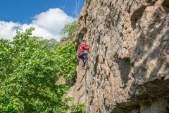 взбираясь утес узлов ropes 2 Молодой альпинист взбирается вертикальный утес гранита весьма спорт Стоковая Фотография