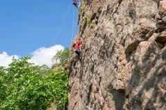 взбираясь утес узлов ropes 2 Молодой альпинист взбирается вертикальный утес гранита весьма спорт Стоковые Фотографии RF