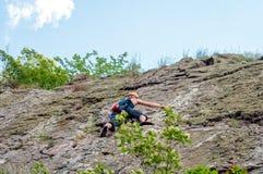 взбираясь утес узлов ropes 2 Молодой альпинист взбирается вертикальный утес гранита весьма спорт Стоковые Изображения
