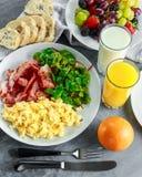 Взбитое яйцо утра, завтрак бекона с апельсиновым соком, молоком, плодоовощ, хлебом на белой плите Стоковая Фотография RF