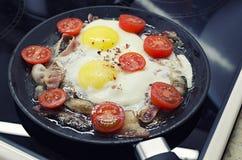 Взбитые яйца варя в сковороде, варя на керамической плите, яичницах с беконом и томате стоковое фото