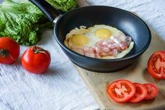 Взбитые яйца и бекон на сковороде на конце-вверх таблицы Стоковая Фотография RF