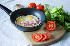 Взбитые яйца и бекон на сковороде на конце-вверх таблицы Стоковые Фотографии RF