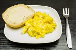 Взбитые яйца и кусок хлеба с маслом на белой плите Стоковая Фотография